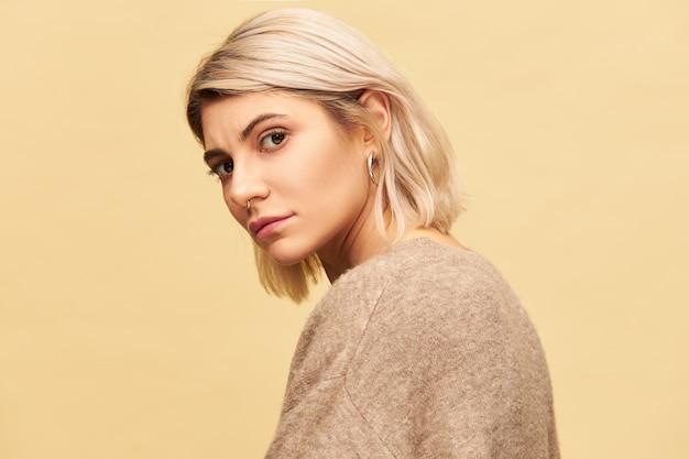Pół-profilowe zdjęcie pięknej młodej kobiety z fryzurą bob, pozującą patrząc oczami pełnymi wyrzutu i podejrzliwości. wyraz twarzy, emocje, reakcje i uczucia człowieka