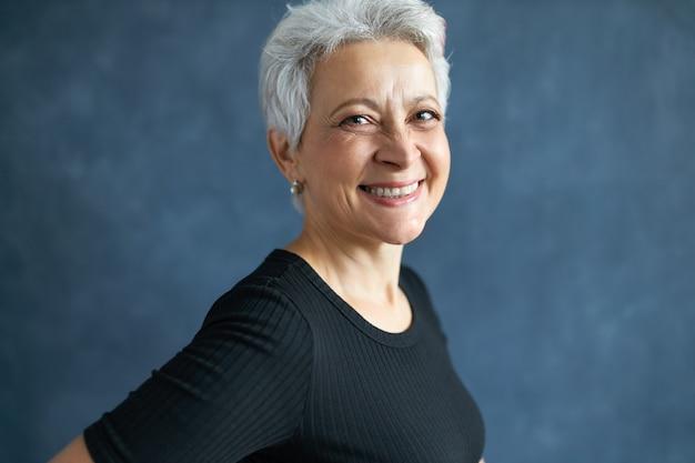 Pół-profilowe zdjęcie wesołej atrakcyjnej kobiety w średnim wieku z krótkimi siwymi włosami i zmarszczkami, bawiącej się, śmiejącej się z żartu, uśmiechającej się szeroko do kamery