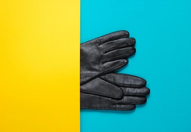 Pół skórzane rękawiczki na żółto-niebieskim stole. koncepcja kreatywnych moda minimalizm. widok z góry