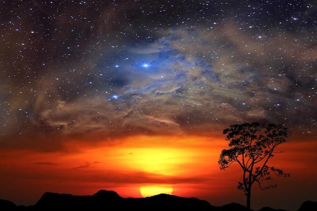 Pół słońca z powrotem czerwona chmura nad górą i galaktyką mgławicy na niebie o zachodzie słońca, elementy tego obrazu dostarczone przez nasa