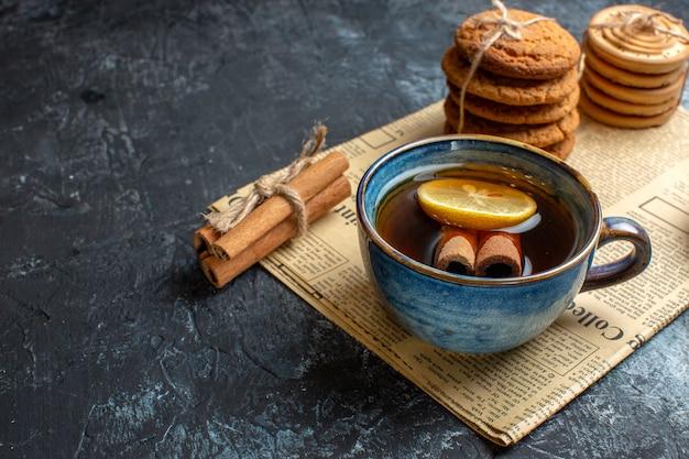 Pół strzału na herbatę z ułożonymi pysznymi ciasteczkami z cytryną cynamonową na starej gazecie na ciemnym tle