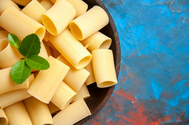 Pół strzału przygotowania obiadu z makaronem makaronowym z zielonym w brązowym garnku na niebieskim tle