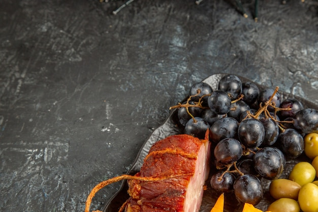 Pół strzału pysznej najlepszej przekąski na wino podawane na brązowej tacy na szarym tle