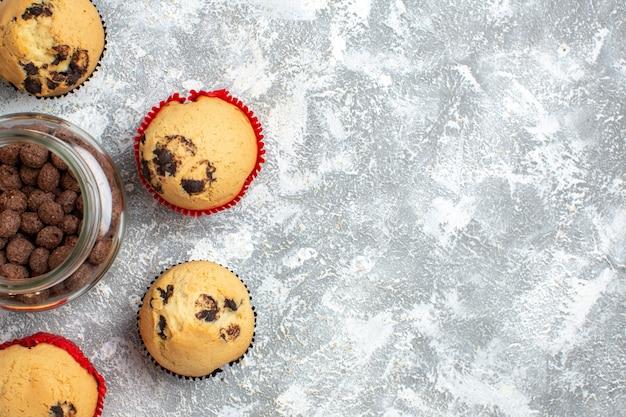 Pół strzału pysznych małych babeczek i czekolady w szklanym garnku obok świątecznego prezentu po prawej stronie na lodowym stole