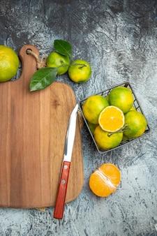 Pół strzału świeżych owoców cytrusowych z liśćmi na drewnianej desce do krojenia pokrojonej w pół formy i nożem na szarym stole z gazety