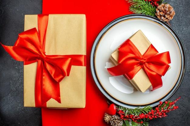 Pół strzału talerze obiadowe z prezentem i na czerwonej serwetce i gałęziach jodły z dekoracyjnym stożkiem iglastym na ciemnym tle