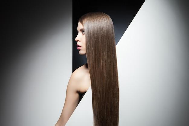 Pół twarzy atrakcyjnej młodej brunetki z długimi lśniącymi włosami