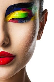 Pół twarzy pięknej kobiety z wielobarwny żywy makijaż oczu na białym tle.