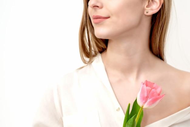 Pół twarzy portret pięknej młodej kobiety rasy kaukaskiej z jednym różowym tulipanem na białym tle