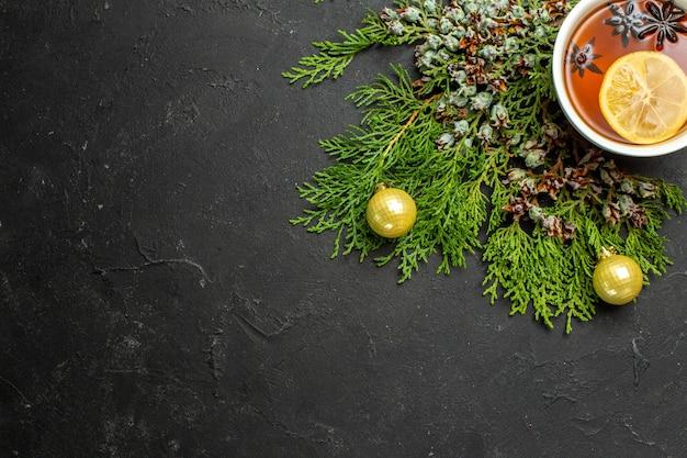 Pół ujęcia filiżanki akcesoriów świątecznych czarnej herbaty i limonek cynamonowych na czarnym tle