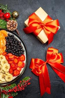 Pół ujęcia kolekcji świeżych owoców na talerzu obiadowym akcesoria do dekoracji gałązek jodły i cyfr na czerwonej serwetce i czerwonej wstążce i prezentu