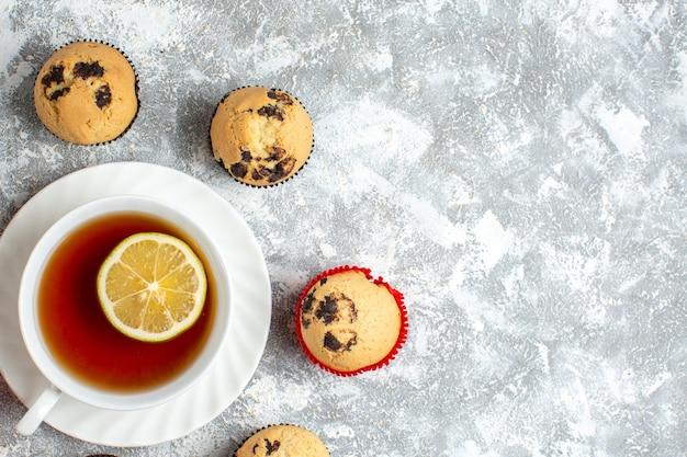 Pół ujęcia pysznych małych babeczek z czekoladą wokół filiżanki czarnej herbaty po prawej stronie na powierzchni lodu
