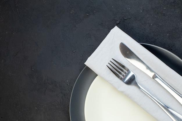 Pół ujęcia sztućców ustawionych na białej serwetce na ciemnym kolorze i białych pustych talerzach w różnych rozmiarach na czarnym tle