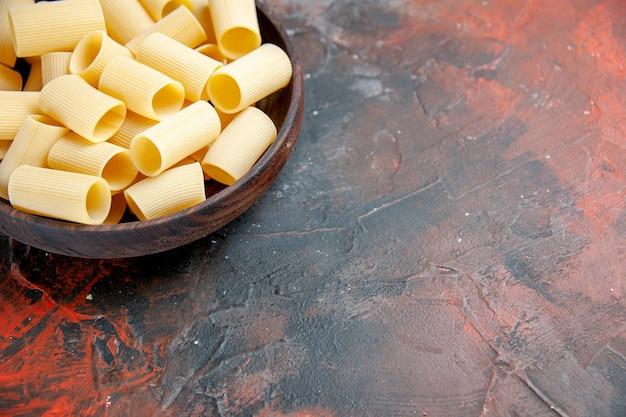 Pół ujęcia z bliska widok niegotowanych makaronów wewnątrz brązowego garnka na czarnym materiale stołowym
