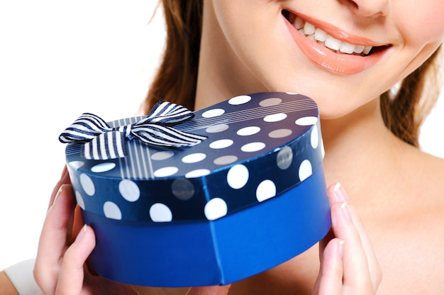 Pół uśmiechnięta twarz młodej kobiety trzymającej niebieskie pudełko