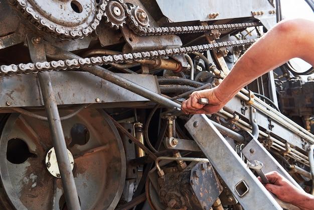 Połącz serwis maszyn, mechanik naprawiający silnik na zewnątrz.
