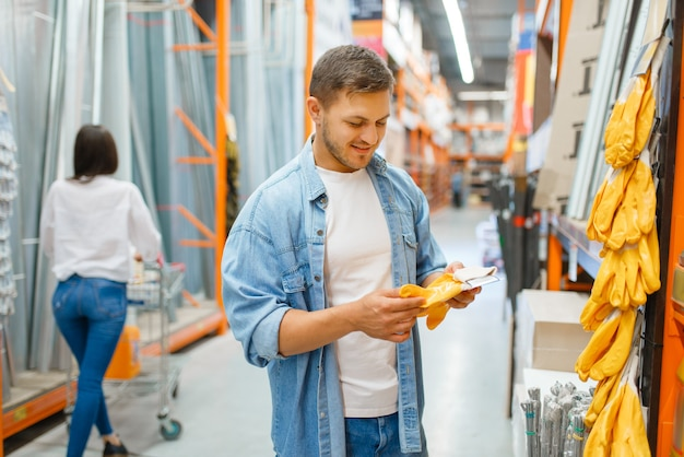 Połącz się z wózkiem kupując rękawiczki i materiały budowlane w sklepie z narzędziami. klienci patrzą na towary w sklepie z artykułami do majsterkowania