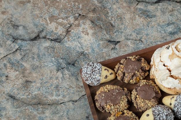 Połączenie ciastek kakaowych i maślanych na drewnianym talerzu.