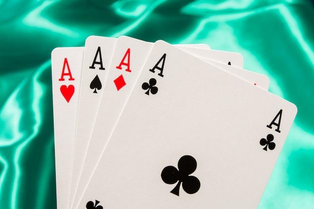 Połączenie kasyna pokerowego z kartami do gry. cztery asy na zielonym materiale