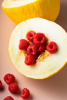 Połączenie świeżych dojrzałych owoców, melona i maliny na delikatnym różu