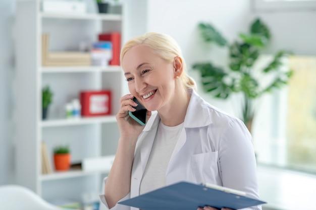 Połączenie telefoniczne. blondynka lekarz uśmiecha się i rozmawia przez telefon