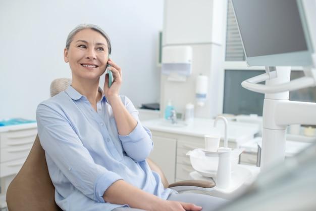 Połączenie telefoniczne. kobieta siedzi w gabinecie dentystycznym i rozmawia przez telefon