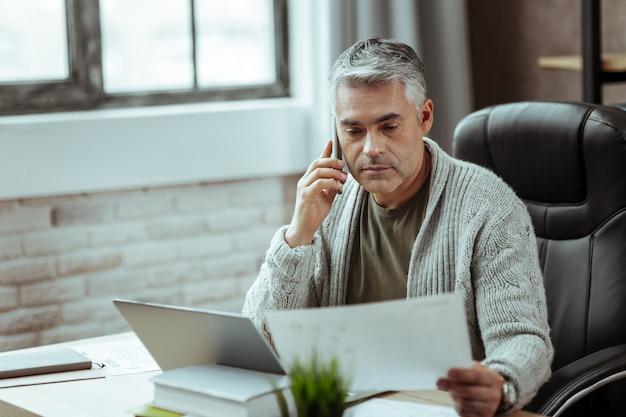Połączenie telefoniczne. mądry dojrzały mężczyzna dzwoniący podczas przeglądania dokumentu