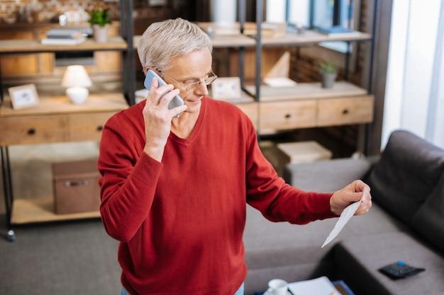 Połączenie telefoniczne. poważny inteligentny starszy mężczyzna trzyma telefon komórkowy i nawiązywanie połączenia, patrząc na notatki