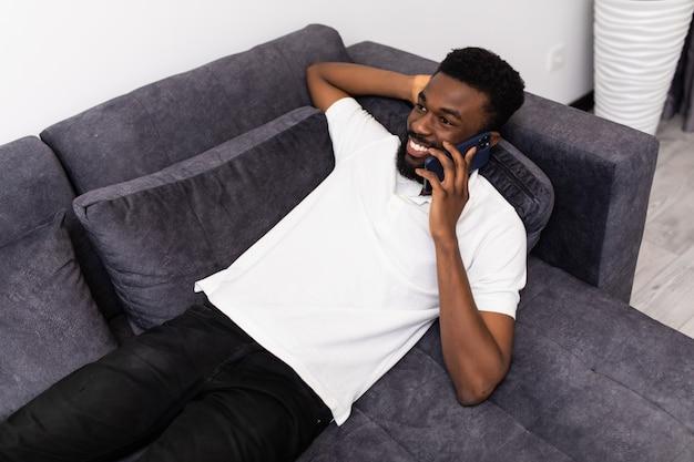 Połączenie telefoniczne. szczęśliwy człowiek afro rozmawia telefon komórkowy leżący na kanapie w domu.
