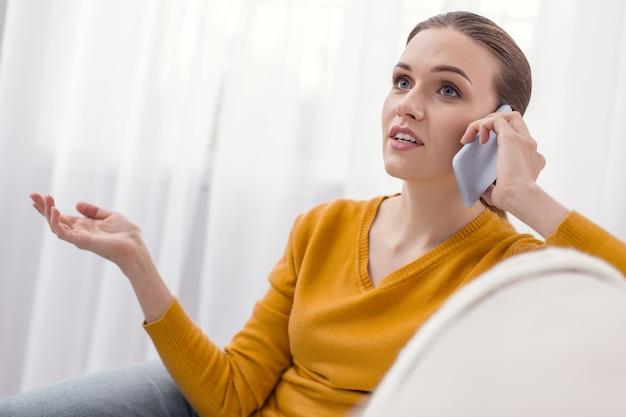Połączenie telefoniczne. urocza, beztroska, miła kobieta gestykulująca, pozująca na świetle i rozmawiająca przez telefon