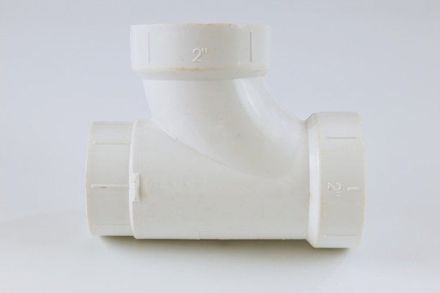Połączenie trójnika żeńskiego z białego polipropylenu z polimeru pvc na białej ścianie