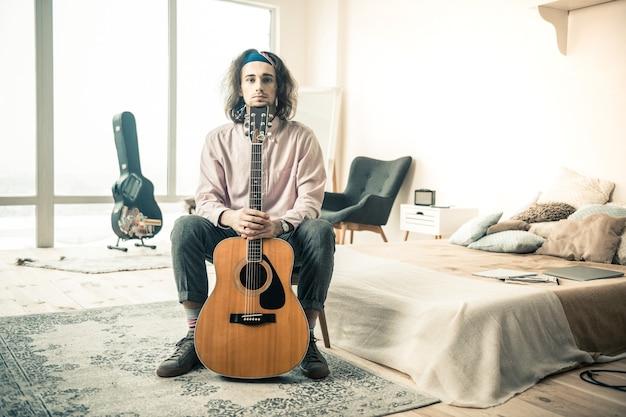 Połączone ręce. młody długowłosy muzyk odpoczywa w stylowej sypialni i opierając się na stojącej gitarze