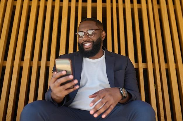 Połączony. ciemnoskóry mężczyzna w garniturze siedzący na ławce ze smartfonem w rękach