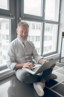 Połączony. mężczyzna siedzący na podłodze i pracujący na laptopie