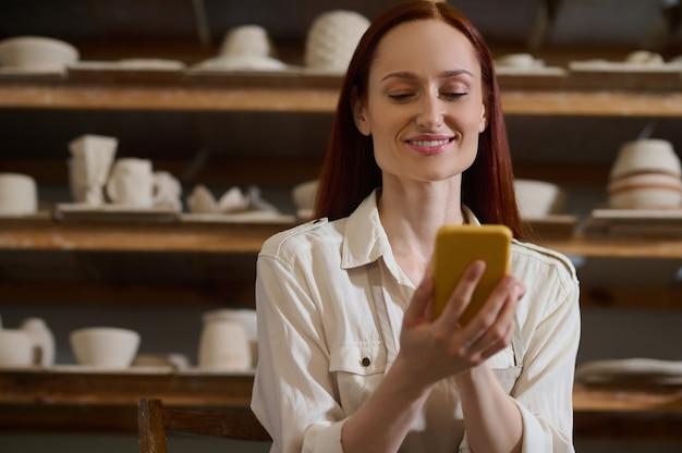Połączony. młoda ładna kobieta ze smartfonem w warsztacie garncarskim
