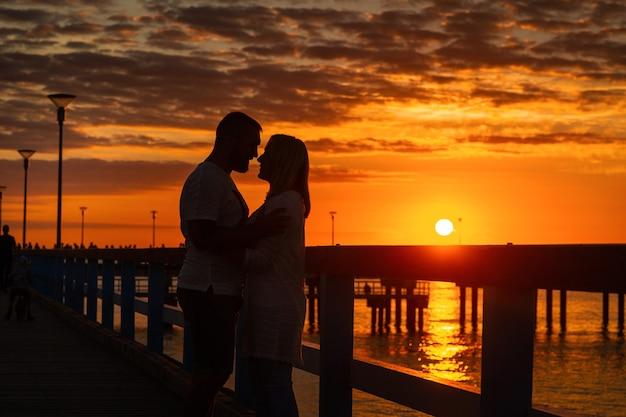 Połąga, litwa. sylwetki zakochanej pary stoją na drewnianym molo nad morzem o zachodzie słońca