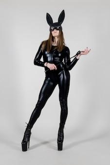 Polak sexy piękna kobieta tancerz pozowanie w lateks kostium i maska czarny królik z biczem na tle. koncepcja zajączek.