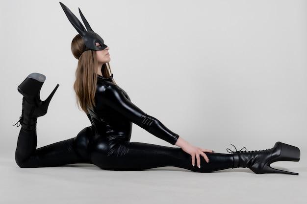 Polak sexy piękna kobieta tancerz pozowanie w lateks kostium na tle. koncepcja zajączek.