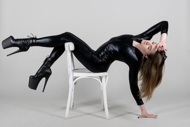 Polak sexy piękna kobieta tancerz pozowanie w lateks kostium na tle.