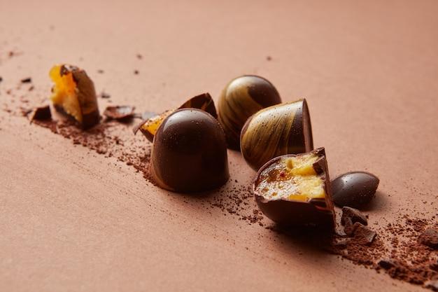 Połamane cukierki czekoladowe z galaretką na brązowym tle