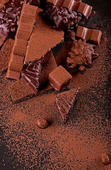 Połamane kawałki czekolady i kakao w proszku na podłoże drewniane