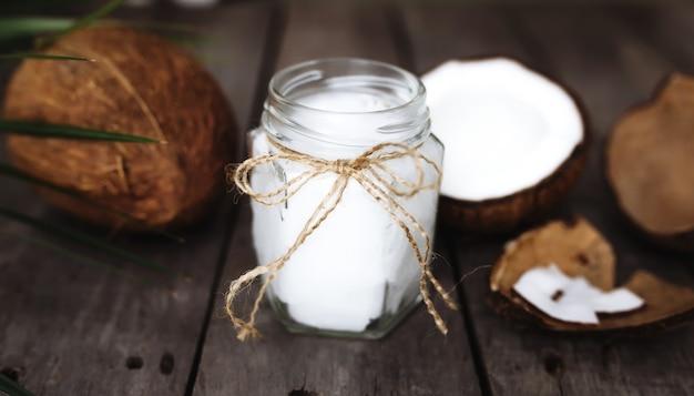 Połamane orzechy kokosowe na szarej drewnianej powierzchni ze słoikiem surowego organicznego oleju kokosowego extra virgin i liściem palmowym. miazga z białego kokosa.