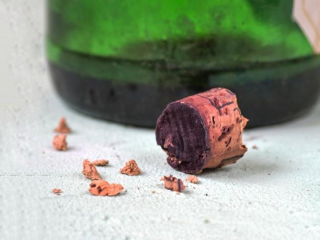 Połamany korek ze starego wina leży na stole.