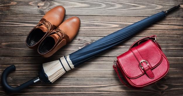 Półbuty skórzane na cały sezon, czerwona torba i składany parasol na drewnianej podłodze. widok z góry. woskowanie akcesoriów kobiecych na deszczową pogodę.