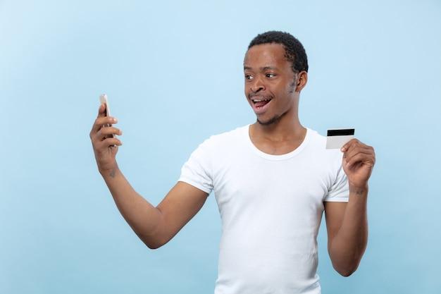 Półdługie portret młodego mężczyzny afro-amerykańskiego w białej koszuli, trzymającego kartę i smartfona na niebieskiej przestrzeni