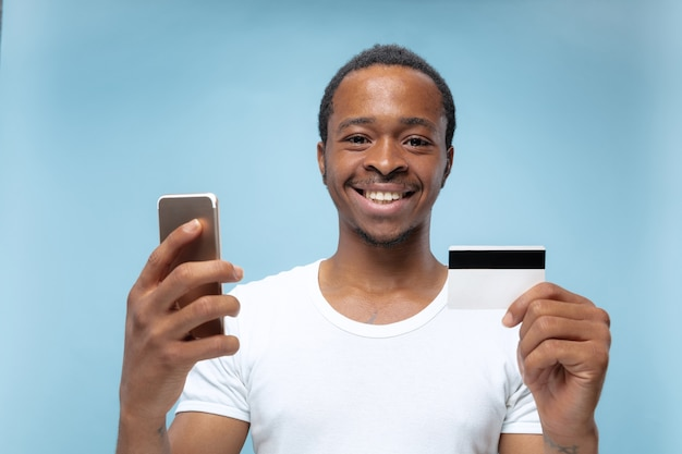 Półdługie portret młodego mężczyzny afro-amerykańskiego w białej koszuli, trzymającego kartę i smartfona na niebieskiej ścianie. ludzkie emocje, wyraz twarzy, reklama, sprzedaż, finanse, koncepcja płatności online.