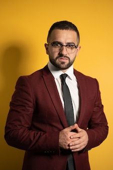 Półdługie portret przystojny mężczyzna stojący pół obrotu w kolorze bordowym i okularach