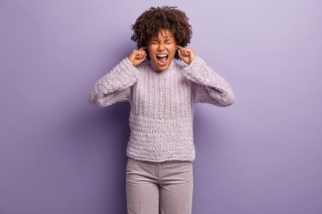Półdługie ujęcie kobiety z depresyjnej rasy mieszanej, zatykającej uszy, nie chcącej słyszeć kłótni, zirytowanej plotkami, nosi dzianinowy sweter i spodnie, stoi nad fioletową ścianą. ignorowanie hałasu