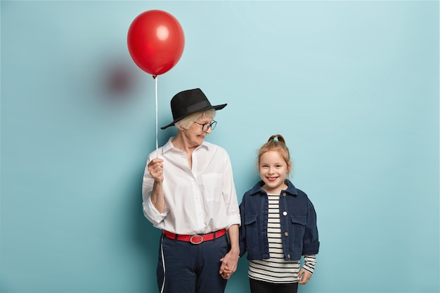 Półdługie ujęcie kochającej babci gratuluje małemu dziecku pierwszego dnia w szkole, trzyma czerwony balon i ma radosne miny. radosna babcia, wnuczka wracają z cyrku w dobrym humorze