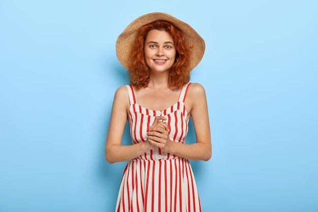 Półdługie ujęcie ładnej uśmiechniętej kobiety w rudej fryzurze, w słomkowym kapeluszu i pasiastej sukience, gotowej na randkę z chłopakiem, trzyma ręce razem, ma zadowolony wyraz twarzy. letnia moda